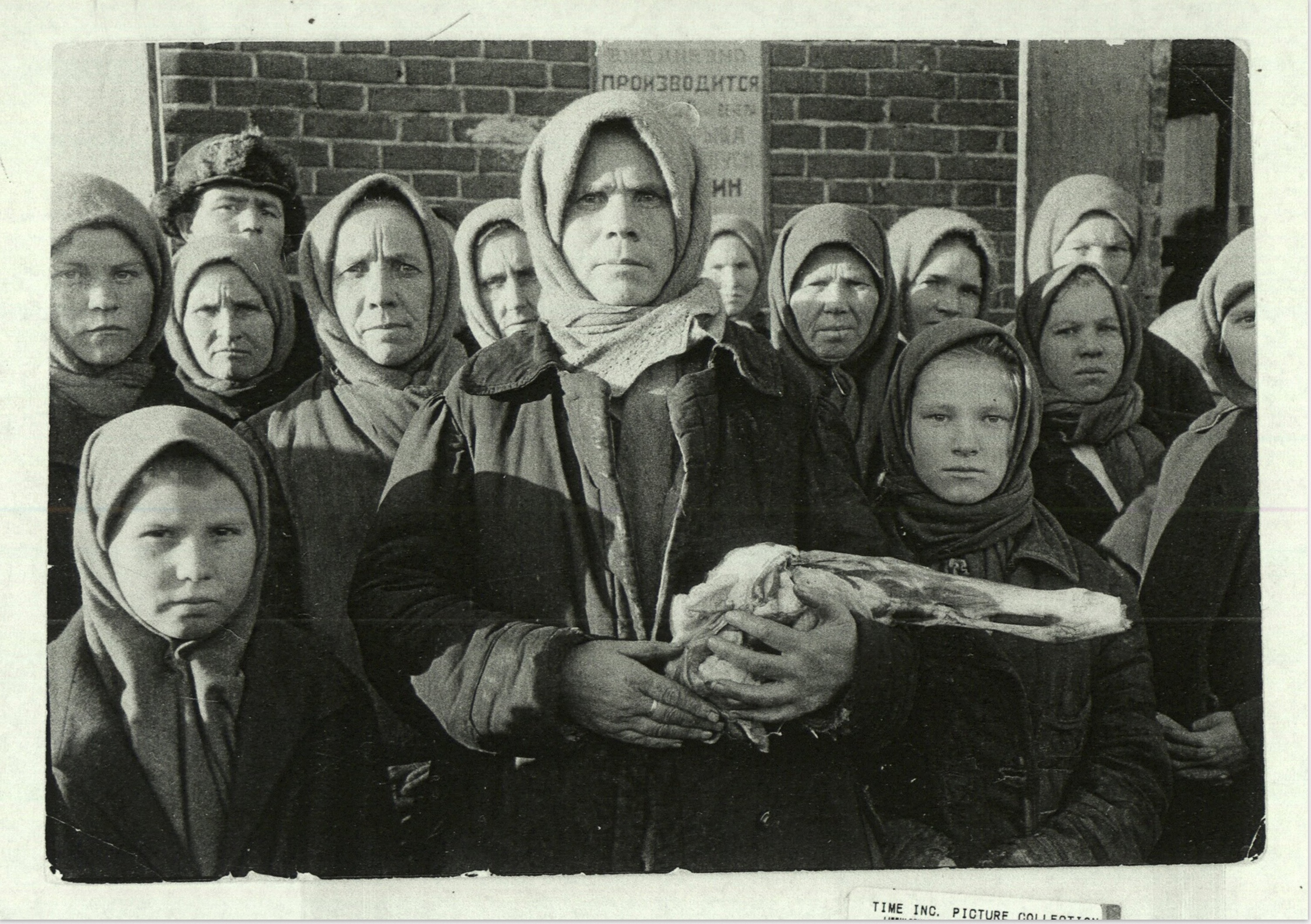 margaret-bourke-white-russian-woman-grimly-holding-a-slab-of-meat-as-other-peasant-women-staunchly-stand-by-in-siberia-magnitogorsk-1931